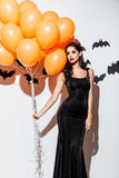 Girl in black halloween costume with eyes closed holding balloons stock images