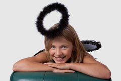 Girl with black halo. Cute little girl in a dress with wings and black halo stock photos