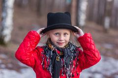 Girl in a black hat with ears and Pavloposadskiye scarf walks in the park cold spring day Stock Photography