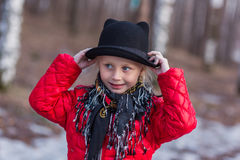 Girl in a black hat with ears and Pavloposadskiye scarf walks in the park cold spring day Stock Photo