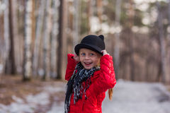 Girl in a black hat with ears and Pavloposadskiye scarf walks in the park cold spring day Royalty Free Stock Image