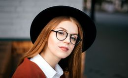 Girl in a black hat and glasses royalty free stock photos