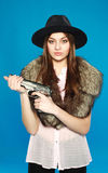 Girl in a black hat with a gun in his hand Royalty Free Stock Photos