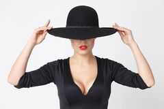 Girl in a black hat. Mysterious girl in a black dress with a neckline and a black hat, photo in the studio, horizontal photo stock image