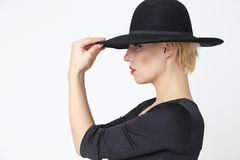 Girl in a black hat. Mysterious girl in a black dress with a neckline and a black hat, photo in the studio, horizontal photo stock photography