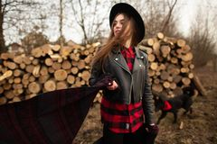 Girl in black hat posing against the background of a firewood and her dog stock photos