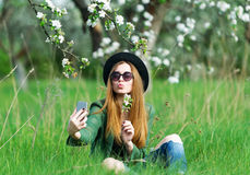 The girl in black hat sits on green meadow. royalty free stock photos