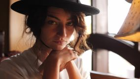 Portrait of a girl in black hat sitting in the cafe and posing for the camera. stock video footage