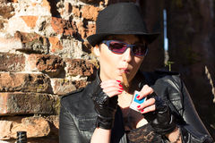Girl in a black hat smokes a cigar. The girl in a black hat smokes a cigar Stock Photo