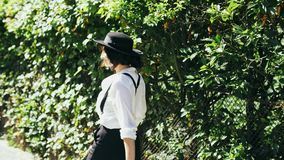 A girl in a black hat and suspenders goes along of green bushes at beautiful day. A girl in a black hat and suspenders with a bag in her hand goes along of green stock footage