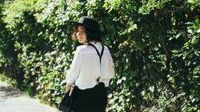 A girl in a black hat and suspenders goes along of green bushes at beautiful day. A girl in a black hat and suspenders with a bag in her hand goes along of green stock video