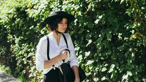 A girl in a black hat and suspenders goes along of green bushes at beautiful day. A girl in a black hat and suspenders with a bag in her hand goes along of green stock video footage