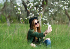 The girl in black hat takes a selfie. Stock Images