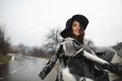 Girl with a black hat walking along the road on a rainy day stock images