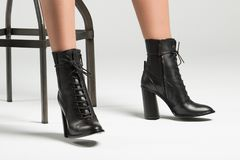 Girl in black high-heeled boots in the studio. A girl is sitting in black high-heeled shoes royalty free stock photography