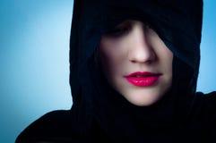 Girl in black hood Stock Images