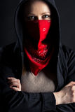 Girl in black hood with a red shawl on his face Royalty Free Stock Image