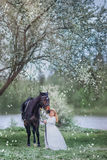 Girl with black horse in blossom garden Royalty Free Stock Images