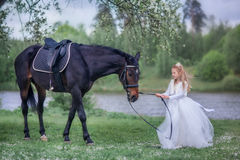 Girl with black horse in blossom garden Stock Images