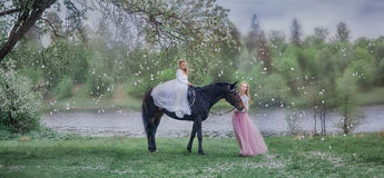 Girl on black horse in blossom garden royalty free stock image