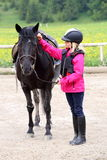 Girl and black horse. Young girl is standing near black horse Royalty Free Stock Photo