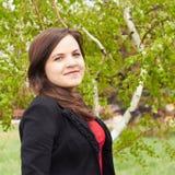 Girl in black jacket. Against birch Stock Image