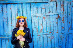 Girl in a black jacket and hat with a bouquet of dandelions Stock Photography