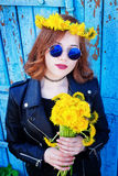 Girl in a black jacket and hat with a bouquet of dandelions Royalty Free Stock Images
