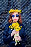 Girl in a black jacket and hat with a bouquet of dandelions Stock Photo