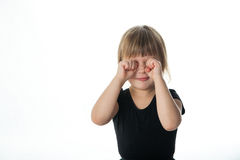 Girl in a black jacket rubs her eyes, white background Royalty Free Stock Photography