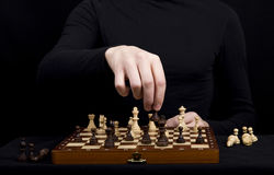 man in a black jacket transposes a pawn on a wooden chess board Stock Photos