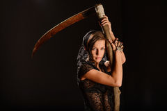 Girl in a black lace smock with scythe of death. Royalty Free Stock Images