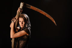 Girl in a black lace smock with scythe of death. Royalty Free Stock Photos