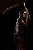 Girl in a black lace smock with scythe of death. Stock Image