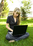 The girl in black, on the lawn with a laptop Stock Photography
