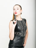 Girl in black leather dress with braided hair is holding a gun Stock Images
