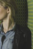 Girl in Black Leather Jacket and Blue Denim Button Up Dress Shirt Leaning on Green Wall Stock Photo