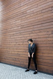 Girl in a black leather jacket near the wooden wall. Girl in a black leather jacket near Stock Image