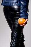 The girl in black leather pants with an orange in his hand Stock Photo