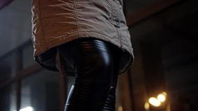A girl in black leggings, sneakers and a long coat goes through the night city. Close up. The camera moves from foot to face