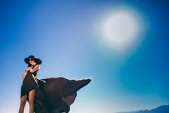 Girl in black long dress on a background of blue sky Stock Images