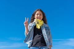 Girl with black long hair against the clear blue sky smiling looking to the camera showing fingers doing victory sign royalty free stock photo