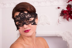 Girl in black mask on white fireplace background Stock Photo