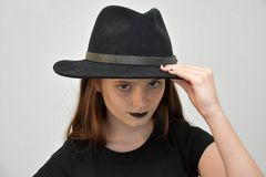 Girl with black  men`s hat and black lips Stock Photos