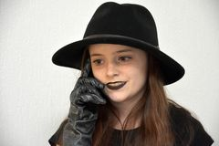 Girl with black  men`s hat and silvery gloves Royalty Free Stock Image