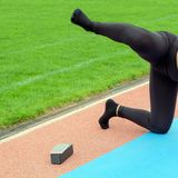The girl in black pants performs sports exercises in the stadium. Muscle training and stretching. The leg is lifted up like a dog. stock photography