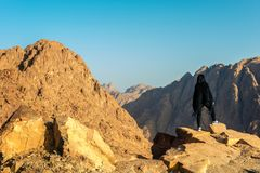 Girl in black poncho stands on the background of mountains. Horizontal frame royalty free stock photography