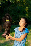 Girl with black poodle Stock Images
