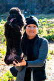 Girl with black poodle Stock Photography