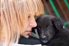 Girl with black puppy outdoor. Young beautiful woman with black puppy outdoor royalty free stock images